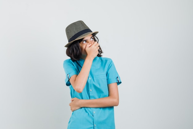 Young lady holding hand on her mouth in blue shirt, hat and looking scared.
