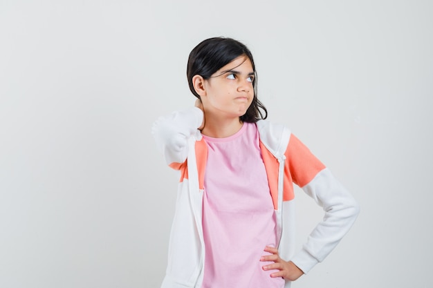 Young lady holding hand on her neck while looking aside in jacket, pink shirt and looking angry.