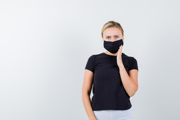Young lady holding hand on mask in t-shirt, pants, medical mask and looking serious