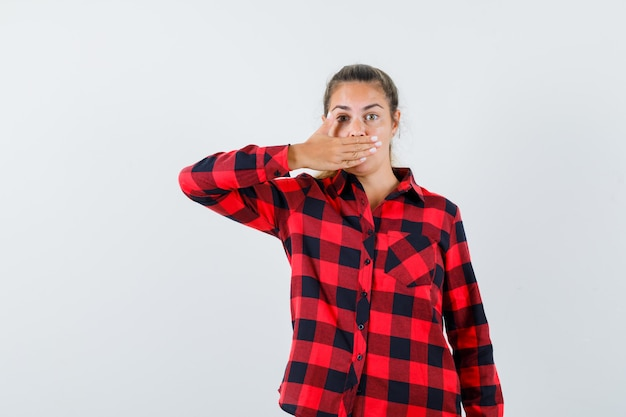 Young lady holding hand on mouth in casual shirt and looking scared , front view.