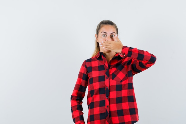 Young lady holding hand on mouth in casual shirt and looking scared. front view.