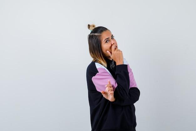 Giovane donna che tiene la mano sulla bocca in felpa con cappuccio e sembra sicura.