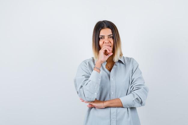Giovane donna che tiene la mano sulla bocca in camicia oversize e sembra soddisfatta. vista frontale.