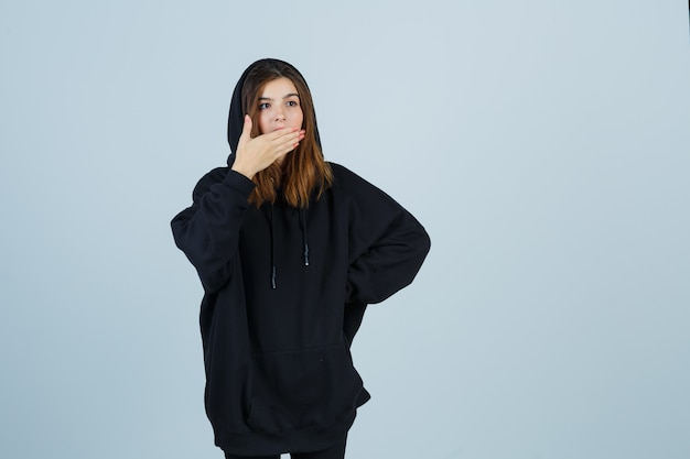Young lady holding hand on mouth in oversized hoodie, pants and looking puzzled , front view.
