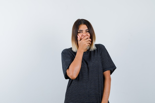 Giovane donna che tiene la mano sulla bocca in abito polo e guardando positivo. vista frontale.