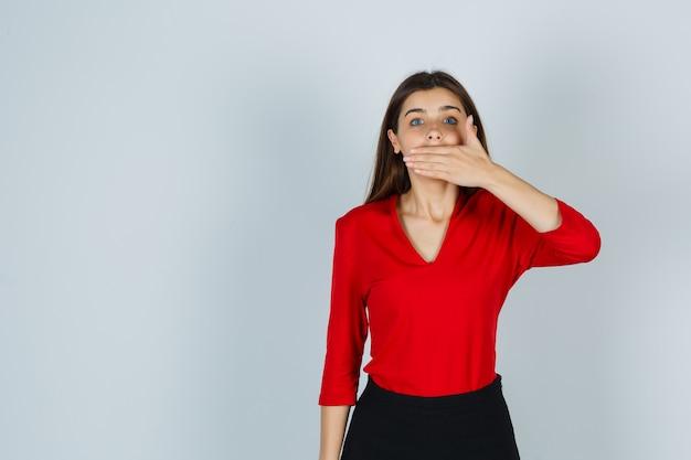 Giovane signora che tiene la mano sulla bocca in camicetta rossa, gonna e che sembra seria