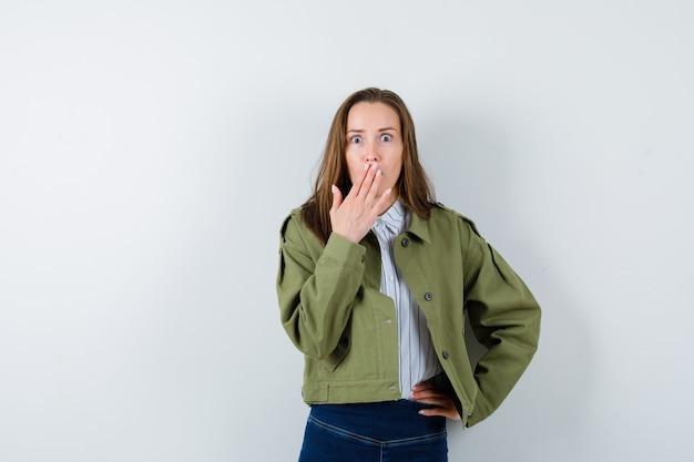Giovane donna che tiene la mano sulla bocca in camicia, giacca e sembra sorpresa. vista frontale.