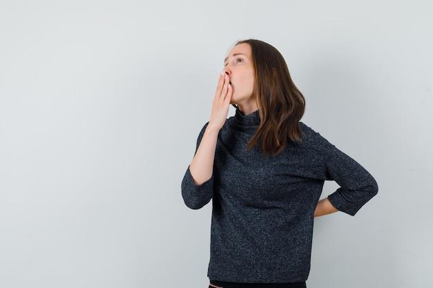 Giovane donna che tiene la mano sulla bocca in camicia e guardando premuroso