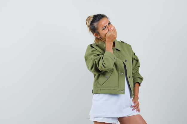 Young lady holding hand on mouth in t-shirt jacket shorts and looking sad