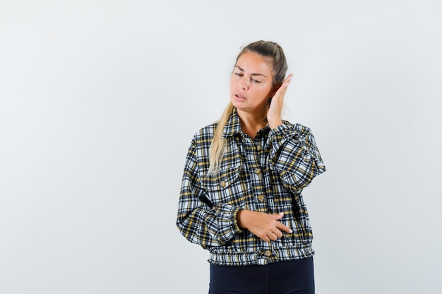 Молодая леди, держащая руку возле глаза в рубашке, шортах и нежный вид. передний план.
