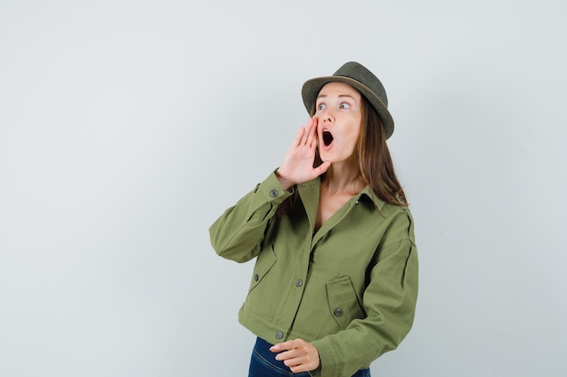 ジャケットパンツ帽子で開いた口の近くで手をつないで、驚いて見える