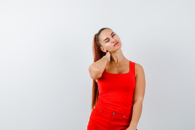 Young lady holding hand behind neck in red singlet, red trousers and looking tired. front view.