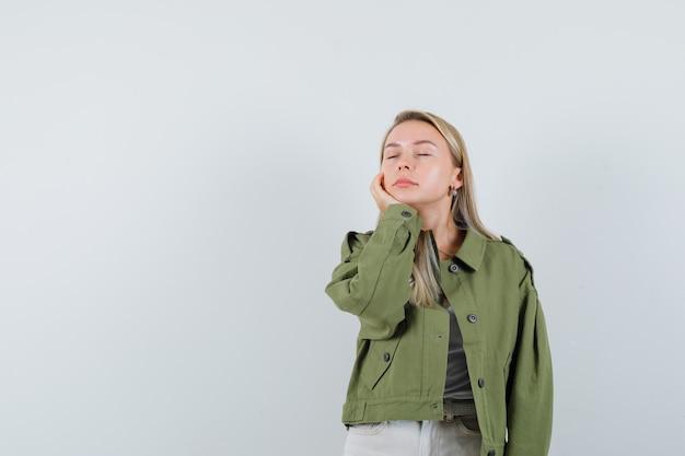 ジャケット、ズボンの頬に手をつないで、平和に見える若い女性。正面図。
