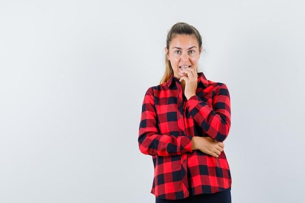 Молодая дама в клетчатой рубашке держит руку за подбородок и выглядит мечтательно