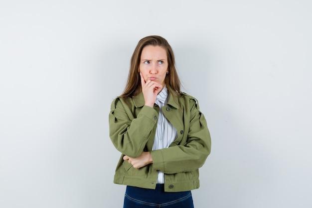 シャツ、ジャケット、躊躇している、正面図で顎に手を握っている若い女性。
