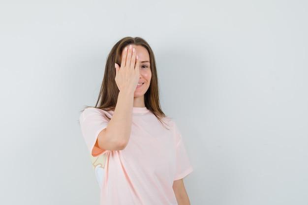 ピンクのtシャツで目をつないで陽気に見える若い女性