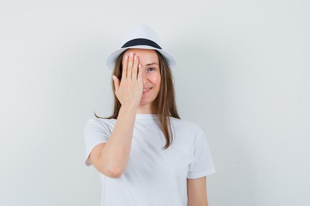白いtシャツの帽子で目をつないで陽気に見える若い女性