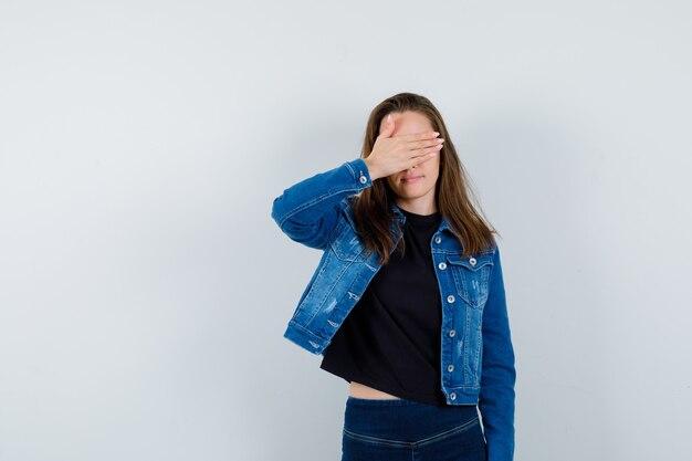Молодая дама держит руку на глазах в блузке, куртке, джинсах и выглядит очаровательно. передний план.