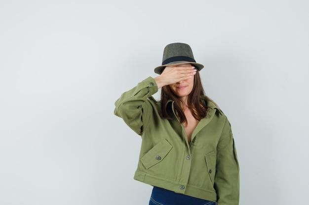 ジャケットのズボンの帽子で目をつないで楽観的に見える若い女性