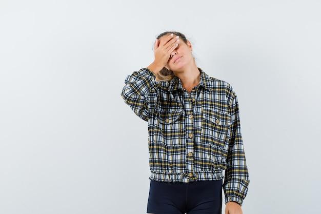 シャツ、ショートパンツで目をつないで、魅惑的な正面図を探している若い女性。