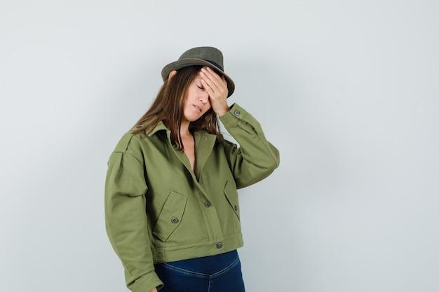 ジャケットのズボンの帽子で額に手を握って落ち込んでいる若い女性