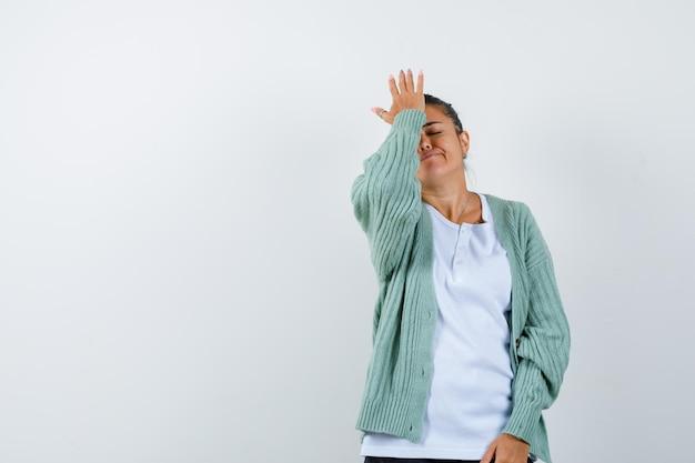 Tシャツ、ジャケットで額に手を握って、疲れているように見える若い女性