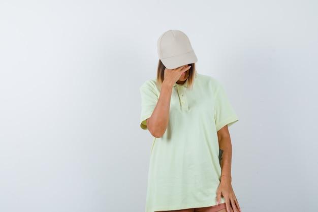 T- 셔츠, 모자를 내려다보고 부끄러워하는 동안 이마에 손을 잡고 젊은 아가씨. 전면보기.