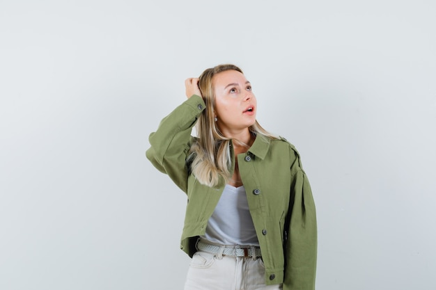 ジャケット、ズボンで頭に手をつないで、夢のような、正面図を探している若い女性。