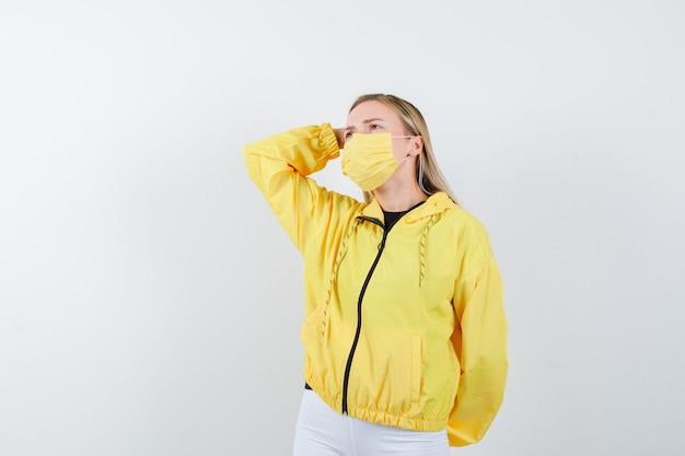 Молодая дама держит руку на голове в куртке, штанах, маске и смотрит задумчиво. передний план.