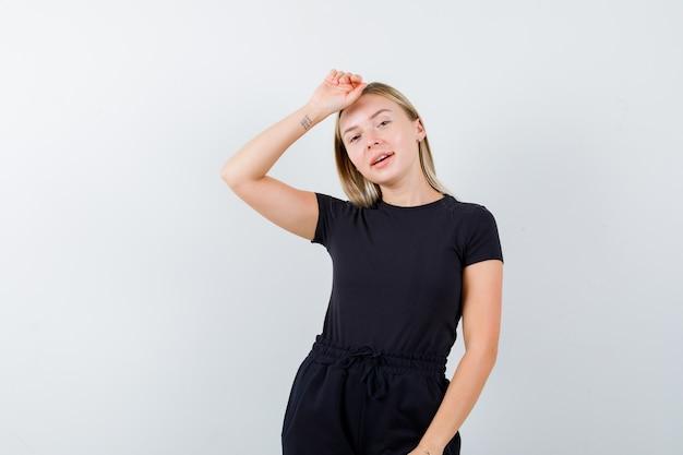 Tシャツ、ズボン、陽気に見える頭に手を保持している若い女性。正面図。
