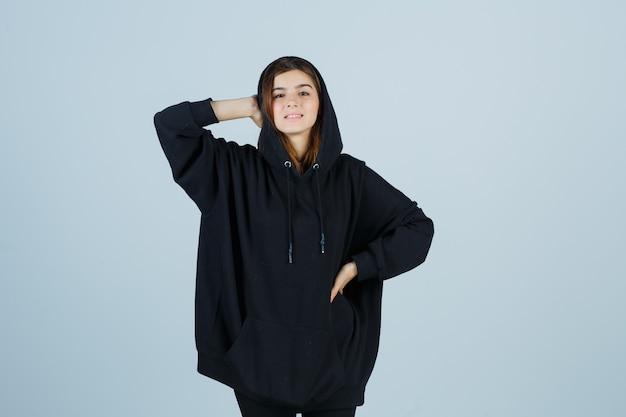 特大のパーカー、パンツ、クールに見える、正面図で腰に手を保ちながら、頭に手を保持している若い女性。