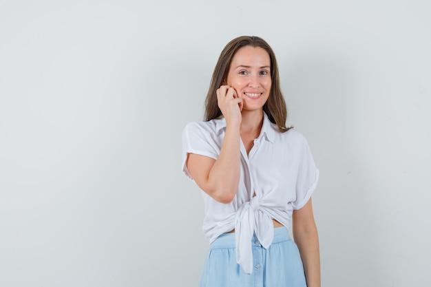 ブラウスとスカートに笑みを浮かべて、かわいく見える間、彼女の頬に手をつないでいる若い女性