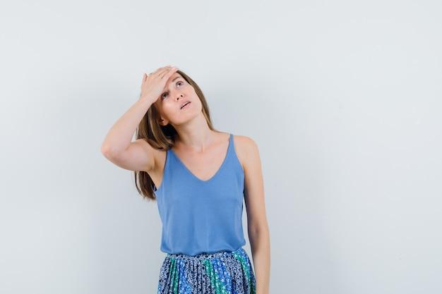 파란색 블라우스, 치마에 그녀의 이마에 손을 잡고 피곤, 전면보기를 찾고 젊은 아가씨.