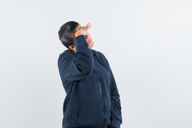 ジャケットを着て目をそらし、焦点を合わせている間、額に手をつないでいる若い女性。正面図。