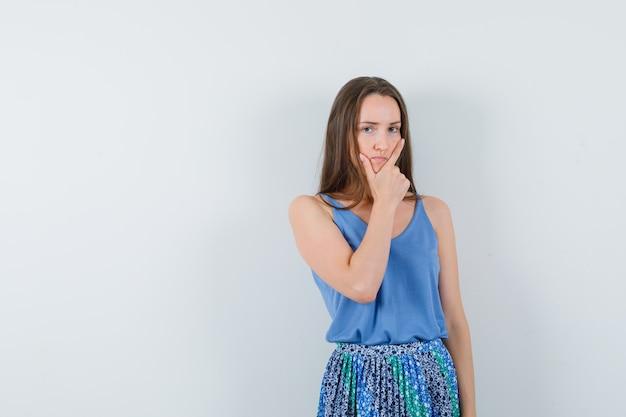 파란색 블라우스, 치마에 생각하고 잠겨있는, 전면보기를 찾고있는 동안 그녀의 턱에 손을 잡고 젊은 아가씨. 텍스트를위한 공간