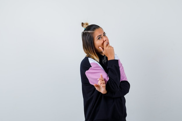 パーカーのセーターで口に手を握り、自信を持って見える若い女性。