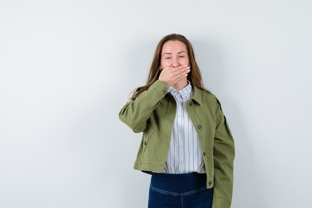 シャツ、ジャケット、幸せそうに見える口に手を握って若い女性。正面図。