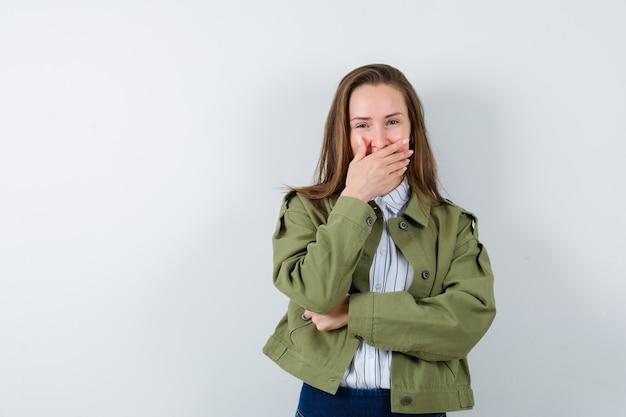 シャツ、ジャケット、陽気に見える口に手を握って若い女性。正面図。
