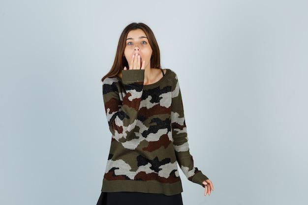 스웨터에 입에 손을 잡고 의아해 찾고 젊은 아가씨