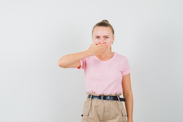 Молодая дама в футболках и брюках держится за рот и выглядит упрямой