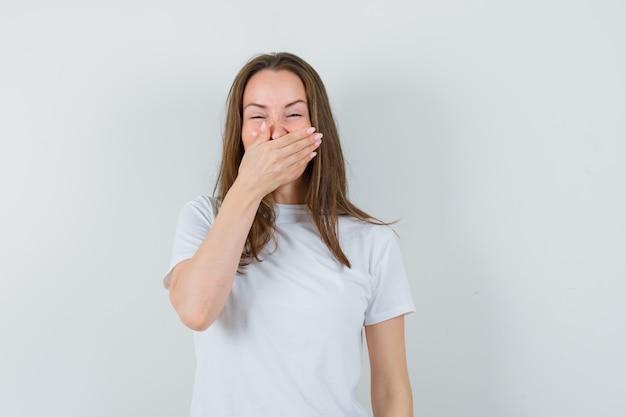 白いtシャツで口に手を握って幸せそうに見える若い女性