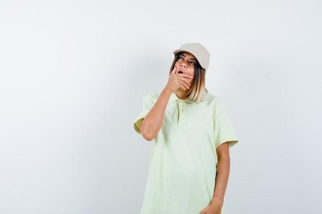 T- 셔츠, 모자를보고 의아해, 전면보기를 찾는 동안 입에 손을 잡고 젊은 아가씨.