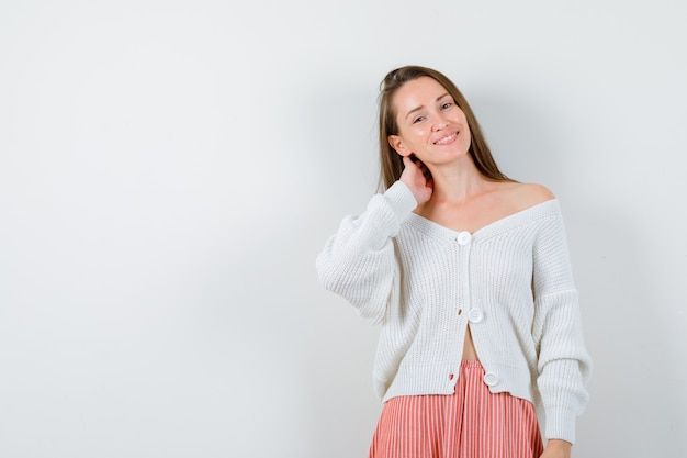 Молодая леди, держащая руку на шее в кардигане и юбке, выглядит счастливой изолированной
