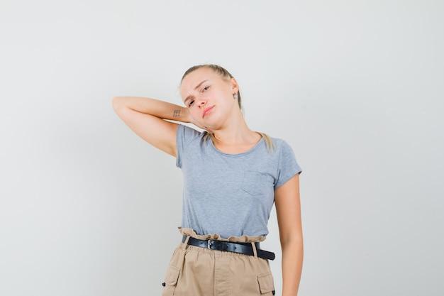 Девушка в футболках и брюках держит руку на шее и выглядит недовольной