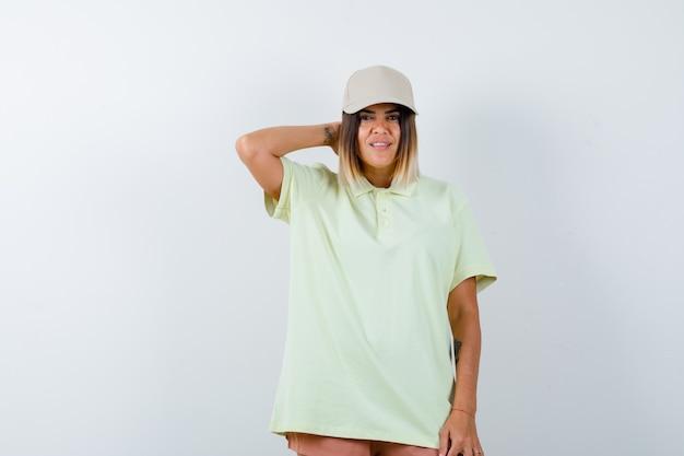 T- 셔츠, 모자, 짧고 자신감, 전면보기에서 포즈를 취하는 동안 목에 손을 잡고 젊은 아가씨.