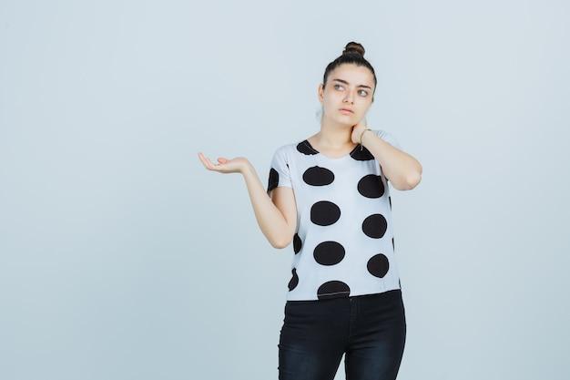 T- 셔츠, 청바지에 뭔가를 잡고 사려 깊은 찾고 척하면서 목에 손을 잡고 젊은 아가씨. 전면보기.