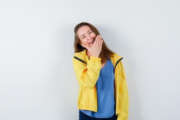 Tシャツ、ジャケットであごに手をかざして、かわいく見える若い女性。正面図。
