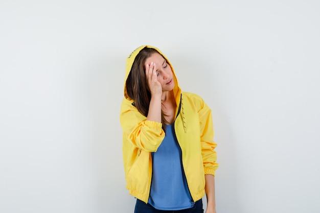 Tシャツ、ジャケットで頭上に手を握って、魅力的に見える若い女性