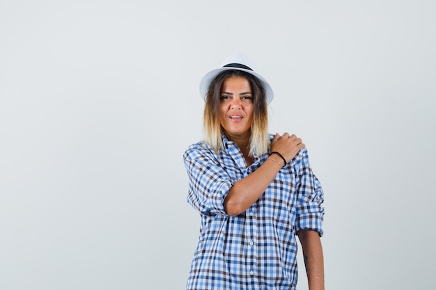 Young lady holding hand on shoulder in checked shirt hat and looking pretty