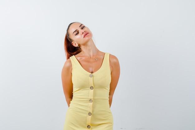 黄色いドレスを着て後ろで手を握り、思慮深く、正面図を探している若い女性。